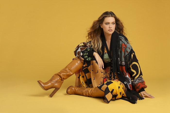 female model wearing layers and camel colored boots on mustard colored seamless