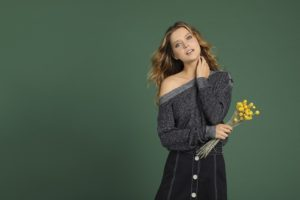 female model holding yellow flowers, wearing off the shoulder sweater, in front of forest green backdrop