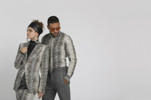 female and male models wearing python print clothing, in front of light gray backdrop