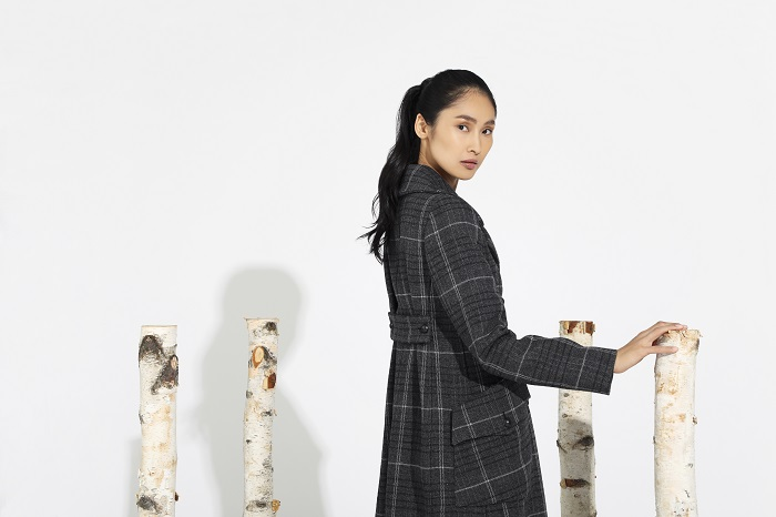 female model with ponytail wearing plaid coat, standing with birch tree pieces