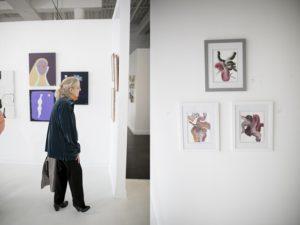 woman walking in front of art gallery wall