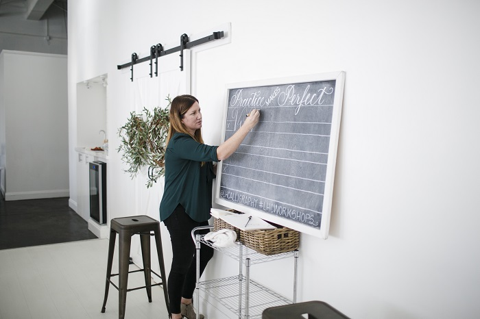 teaching a calligraphy workshop at a chalkboard