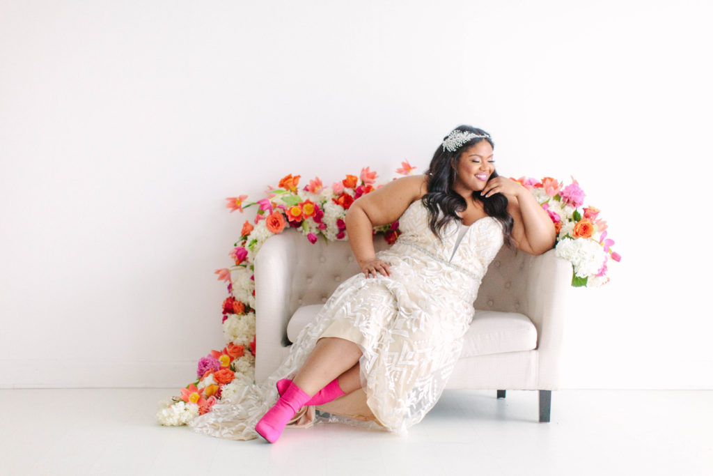 curvy black bride sitting on styled setee, wearing hot pink booties and curvy rose wedding gown