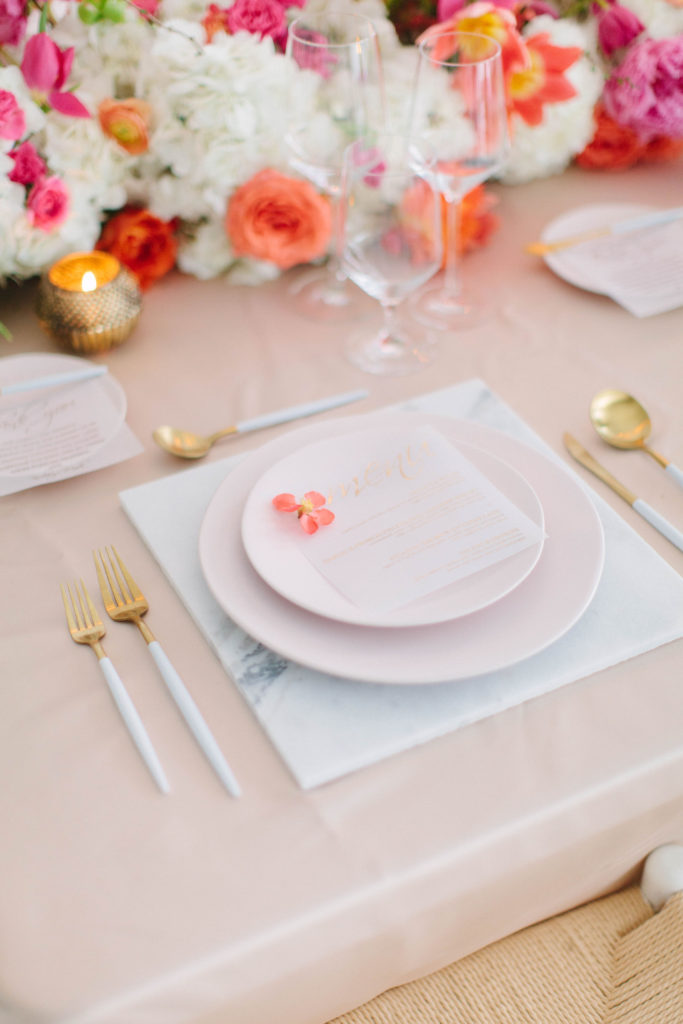 blush colored styled place setting with gold flatware and white marble charger