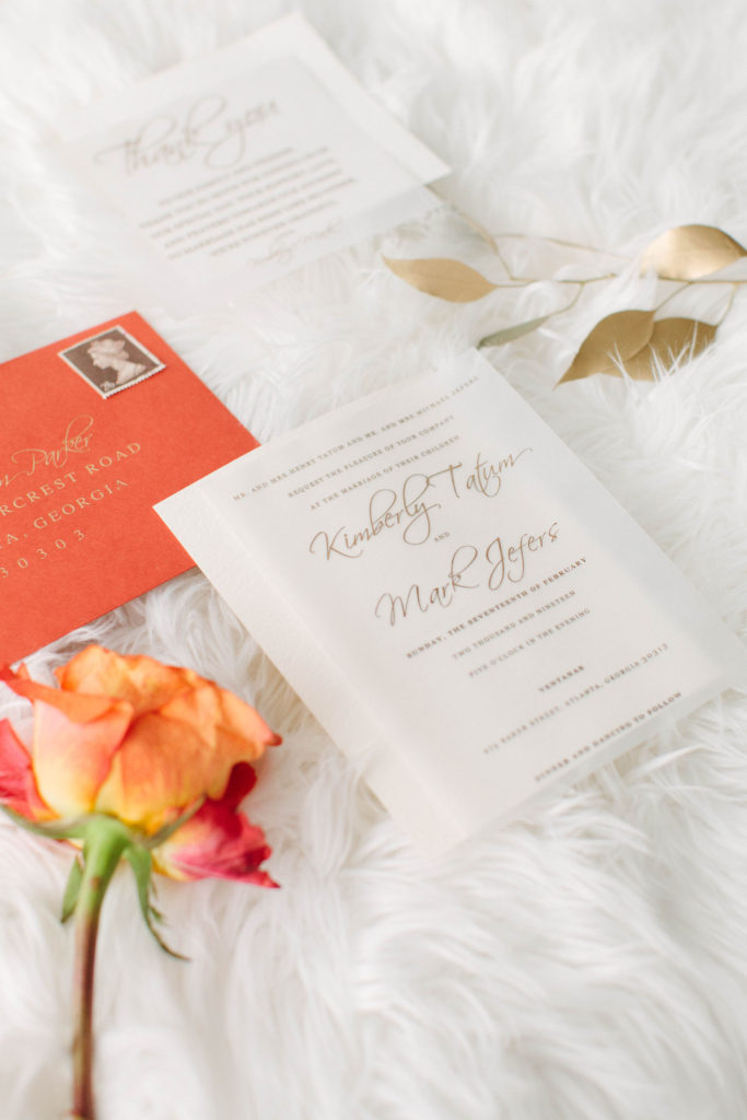 coral wedding stationery suite by The Taylored Design Co., flat lay on white flokati