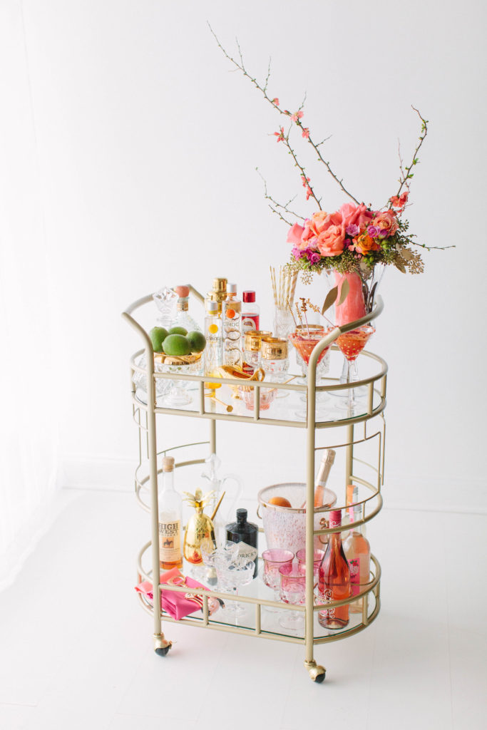 punchy styled bar cart by The Prissy Plate Company, with coral vase, orange cosmopolitans, a gold bowl of limes, and rose and champagne bottles