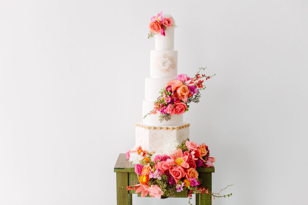 five tier wedding cake with tropical hued florals created by Sweet Details and Stylish Stems
