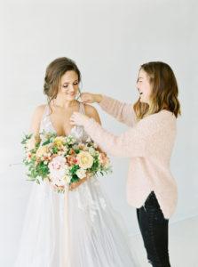 spring bride having her dress adjusted