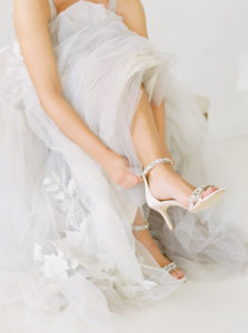sitting bride showing off Badgley Mischka shoes