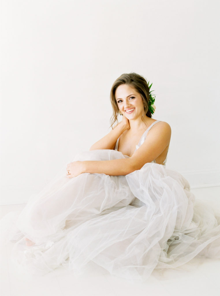 smiling brunette bride sitting on floor