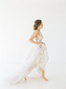 brunette bride walking holding up her dress