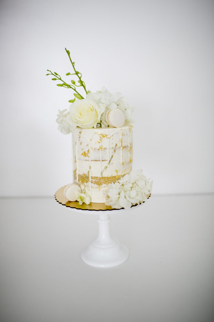 small white and gold cake with pale yellow roses and macarons