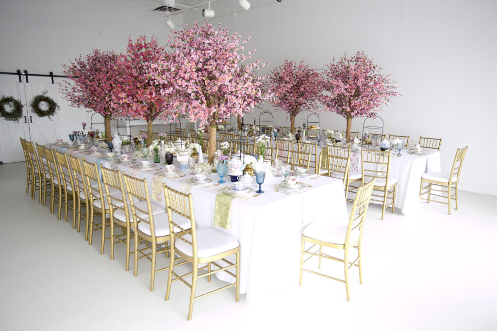 long white tables with gold chairs and cherry blossom centerpieces