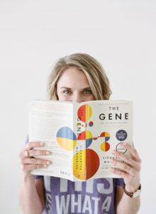 blonde woman peeking over The Gene book