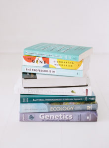stack of science books in white studio space