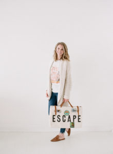 pretty blonde girl holding ESCAPE labeled old fashioned suitecase