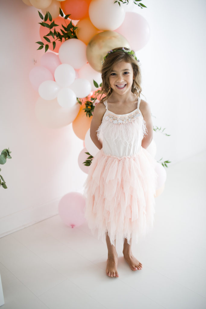 little girl wearing ballet dress, with balloon installation behind her