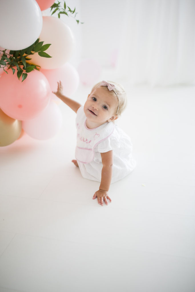 baby girl holding balloons