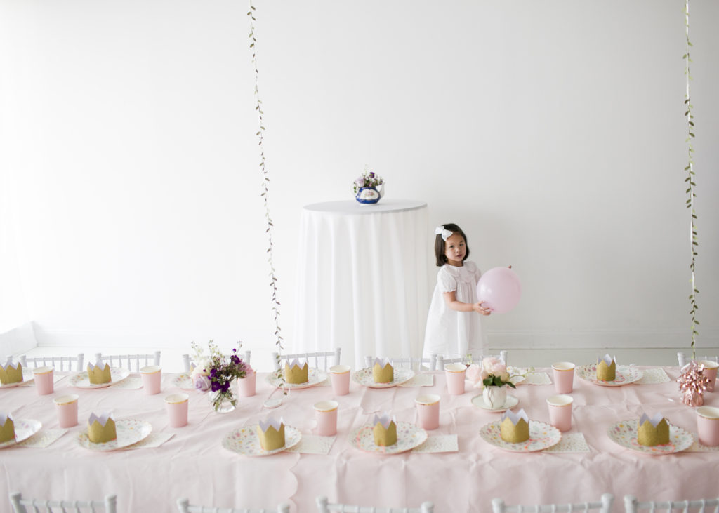 little girl holding a pink balloon, garden tea party tables in foreground