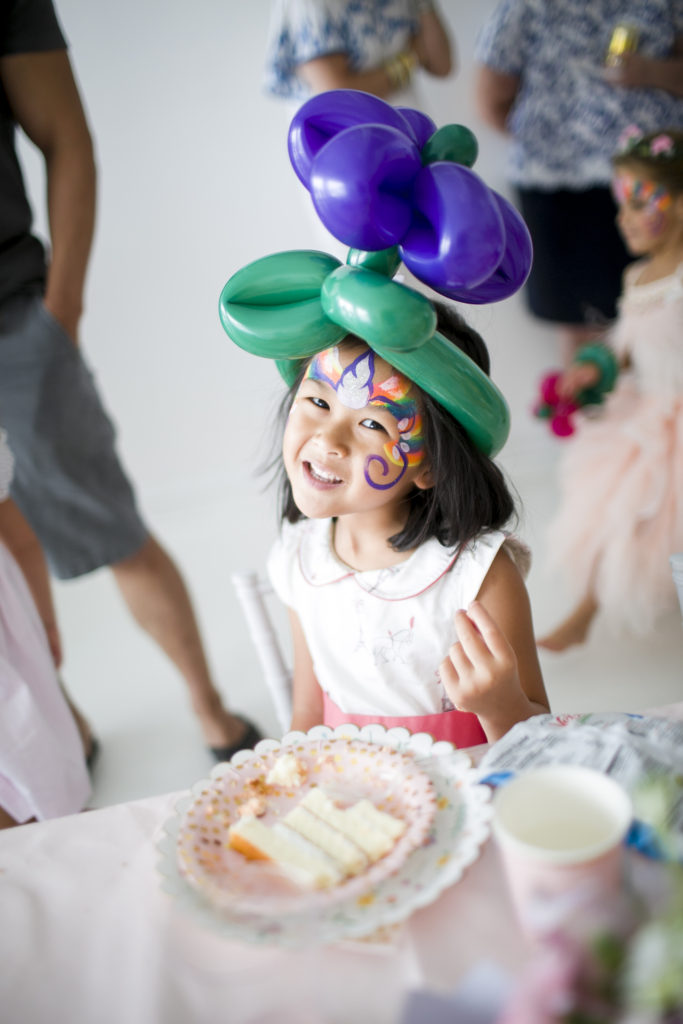 little girl with painted face wearing a balloon flower hat