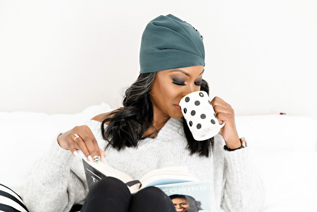 person, coffee cup, Michelle Obama book, striped pillow, fuzzy sweater